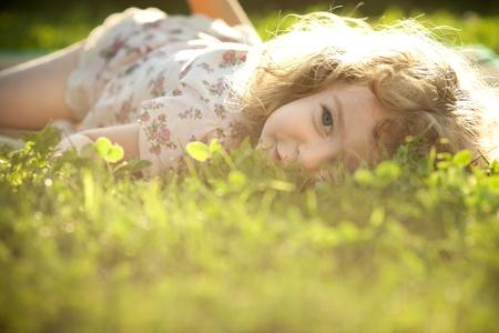 lying in grass: Hermoso ni�o acostado en una hierba en un prado de primavera bajo el sol