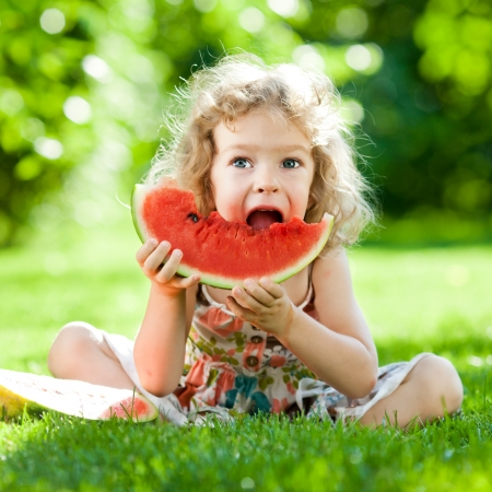 Happy child sitting on green grass and eating watermelon outdoors in spring park against natural sunny blurred background Foto de archivo
