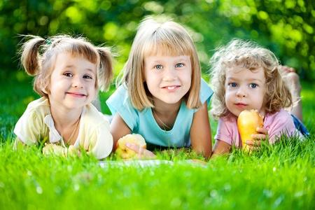 niños jugando en el parque: Grupo de niños sonrientes felices jugando al aire libre, en la primavera de parque Foto de archivo