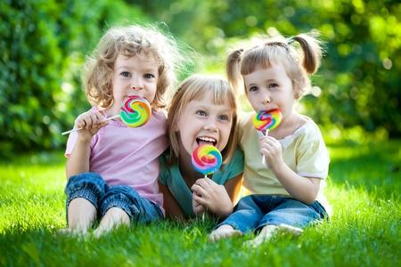 piruleta: Grupo de niños felices comiendo fruta cae al aire libre, en la primavera de parque
