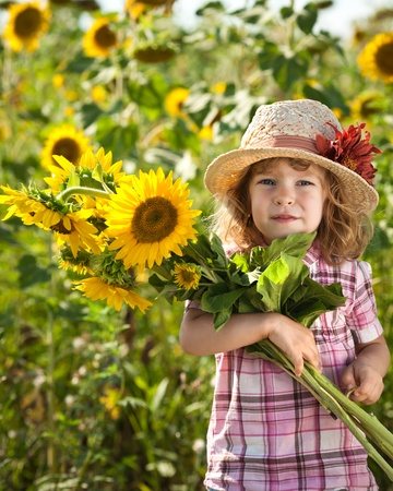 Happy smiling child with bunch of sunflowers in spring field photo