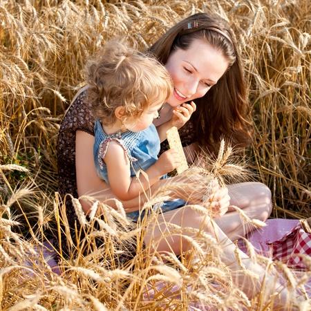 familia comiendo: Feliz mujer y niño que come el pan de trigo de primavera en el campo Foto de archivo
