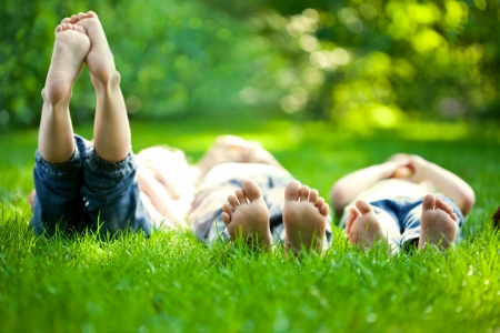 Group of happy children lying on green grass outdoors in spring park Stok Fotoğraf - 12580808