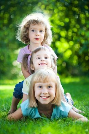 piramide humana: Grupo de ni�os felices jugando al aire libre en la primavera de parque Foto de archivo