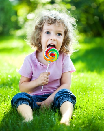 Happy child eating lollipop on green grass outdoors in spring park photo