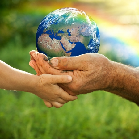 Hands of senior man and baby holding Earth against a rainbow in spring  Ecology concept