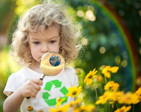 Kind met recycle-symbool op T-shirt te kijken naar de lente bloemen tegen regenboog Dag van de Aarde begrip Elementen van deze afbeelding geleverd door NASA
