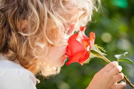 Child with rose flower in spring garden