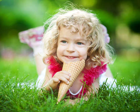 Happy smiling child eating ice-cream on green grass outdoors in spring park photo