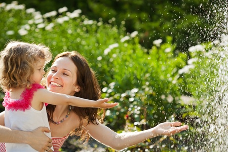 Woman with child playing against splashes of water in the summer photo