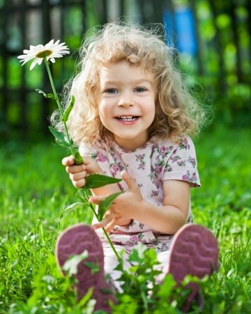 children playing outside: Happy smiling child with flower sitting on green grass outdoors in spring garden