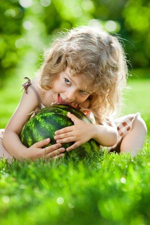 Glückliches Kind spielt mit Wassermelone im Freien im Frühjahr Park