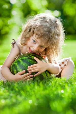 Happy child playing with watermelon outdoors in spring park photo