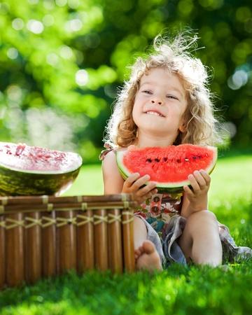 comiendo frutas: Niño feliz sonriendo al aire libre, comer sandía en la primavera de parque