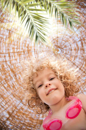Low angle view of happy smiling child on summer vacations by the sea photo