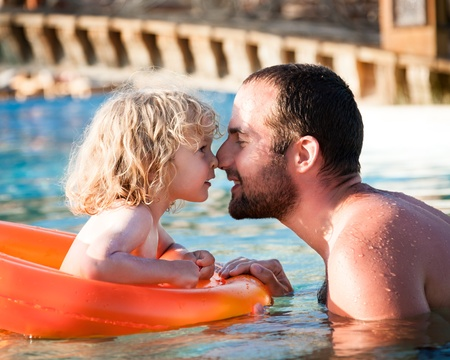 Happy child playing with father in blue water of swimming pool on a tropical resort at the sea  Summer vacations concept