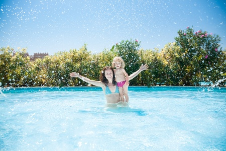 Happy family playing in blue water of swimming pool on a tropical resort at the sea. Summer vacations concept photo