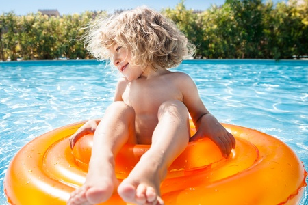 Happy child playing in blue water of swimming pool on a tropical resort at the sea. Summer vacations concept