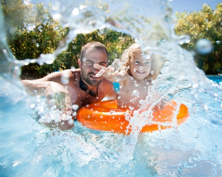 Happy family playing in blue water of swimming pool on a tropical resort at the sea. Focus on children`s hand and splash, shot was taken with waterproof box photo
