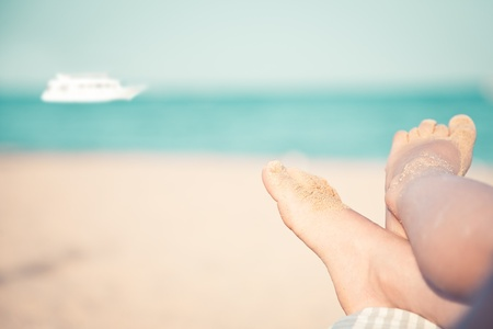 sunburnt: Children s feet at the beach against sea and ship  Summer vacations concept Stock Photo