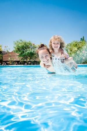 海の夏の休暇で熱帯リゾートのスイミング プールで女性と遊んで喜んでいる子供