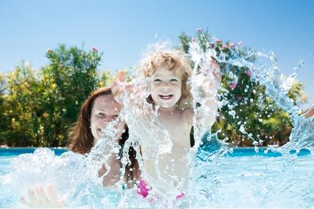 splash pool: Familia feliz jugando en el agua azul de la piscina en un resort tropical en el mar de verano Vacaciones en concepto de Foto de archivo