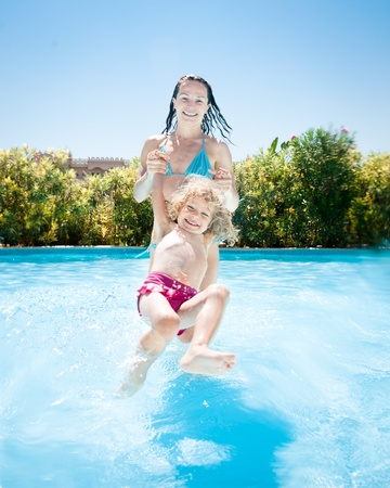 Happy family playing in blue water of swimming pool on a tropical resort at the sea  Summer vacations photo