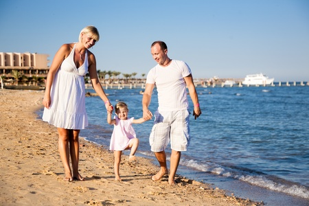three palm trees: Happy smiling family  man, women and kid playing at the sea beach  Summer vacations concept