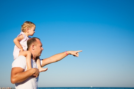 Happy child playing with father at the sea against blue sky background  Summer vacations concept photo