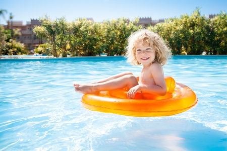 Happy kid swimming in blue water of pool on a tropical resort at the sea  Summer vacations photo