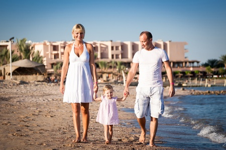 Happy family walking at the beach  Summer vacations photo