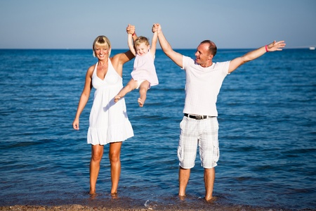 Happy family playing at the beach  Summer vacations photo