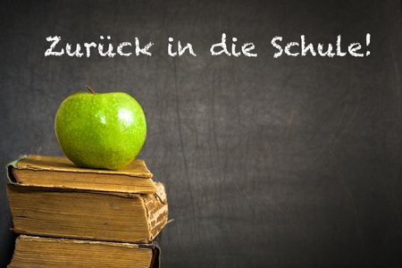 Green apple on old book against blackboard with text  Back to school   in the German language  School concept photo