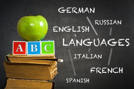 spanish language: Green apple and ABC on old books against blackboard with with the drawn scheme of studying of languages  School concept