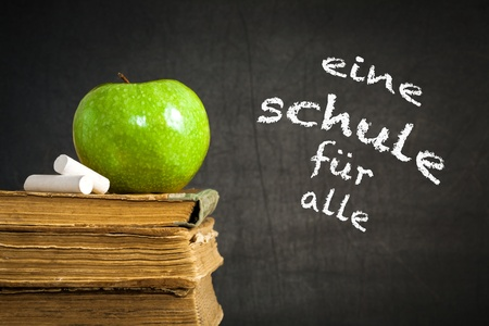 german food: Green apple and chalk on old books against blackboard with text  school for everybody  in the German language  School concept