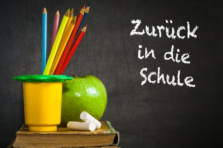 Multicolor pencils, chalks and green apple on old book against blackboard with text  Back to school   in the German language  School concept photo