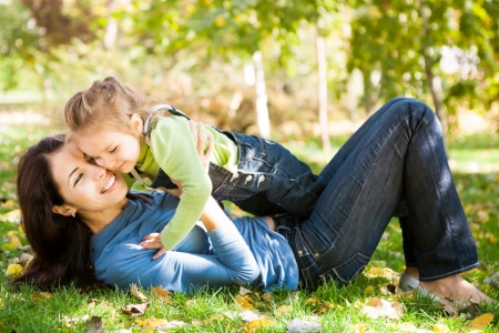 enjoy space: Full length portrait of woman with child lying on fall leaves in autumn park Stock Photo