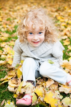Happy child playing in yellow autumn leaves outdoors Stock Photo - 13881836