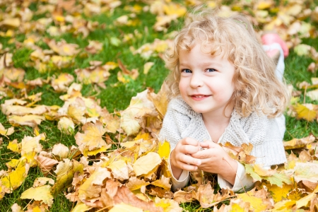 Happy smiling child lying on yellow autumn leaves outdoors photo