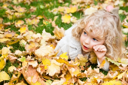 Beautiful child lying on yellow maple leaves in autumn park photo