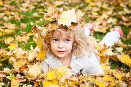 Smiling child in autumn yellow leaves outdoors. Autumn fashion concept photo