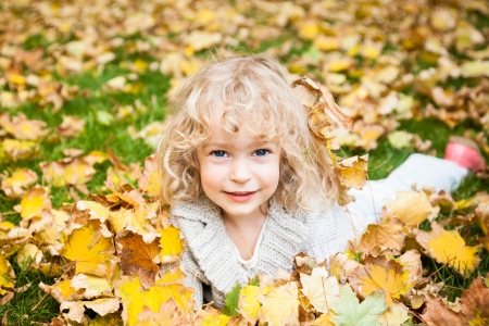 Happy smiling child lying on yellow maple leaves in autumn park photo