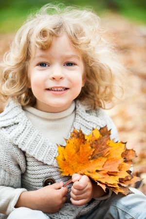 Smiling child sitting on yellow maple leaves in autumn park Stock Photo - 13881883