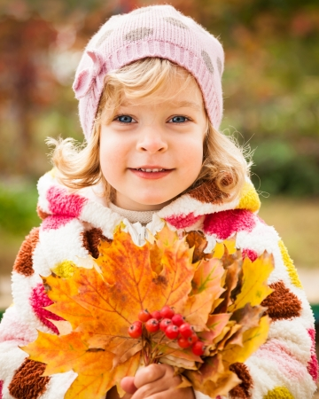 Happy smiling child holding yellow maple leaves in autumn park photo