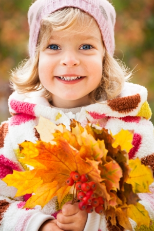 Happy child holding autumn leaves outdoors photo