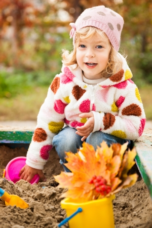 Happy child playing on playground in autumn park. Healthy lifestyles concept photo