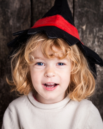 Happy laughing kid in hat of witch. Halloween concept photo