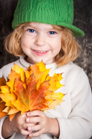 Happy smiling child holding yellow maple leaves. Autumn concept photo