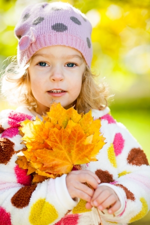 Happy smiling child with yellow maple leaves in autumn park photo