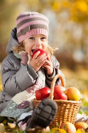 Happy kid eating red apple in autumn park. Healthy lifestyles concept photo